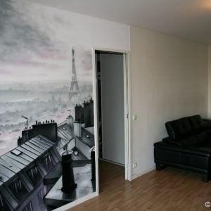 Vue du salon avec la fresque sur le thème des toits de Paris